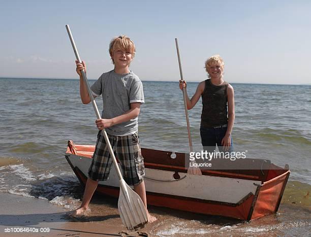 Boys (10-14) with canoe on beach
