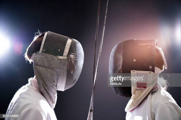 boys with foils fencing against black background - face guard sport stock pictures, royalty-free photos & images