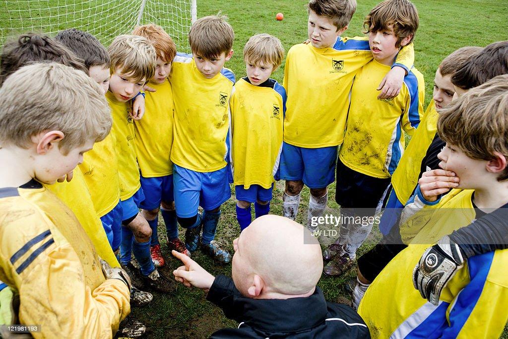 Boys with football coach, high angle : Stock Photo