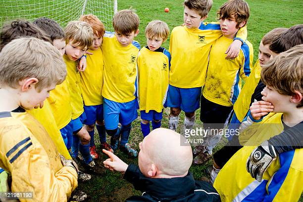 boys with football coach, high angle - kindertijd stockfoto's en -beelden