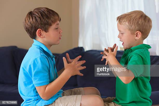 Boys with hearing impairments signing football in American sign language on their couch
