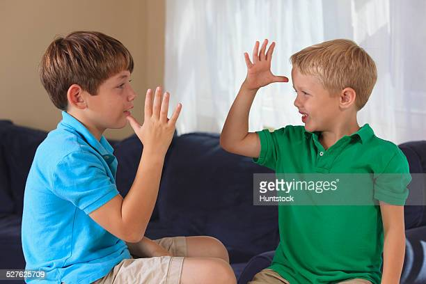 Boys with hearing impairments signing mom, dad or parents in American sign language on their couch