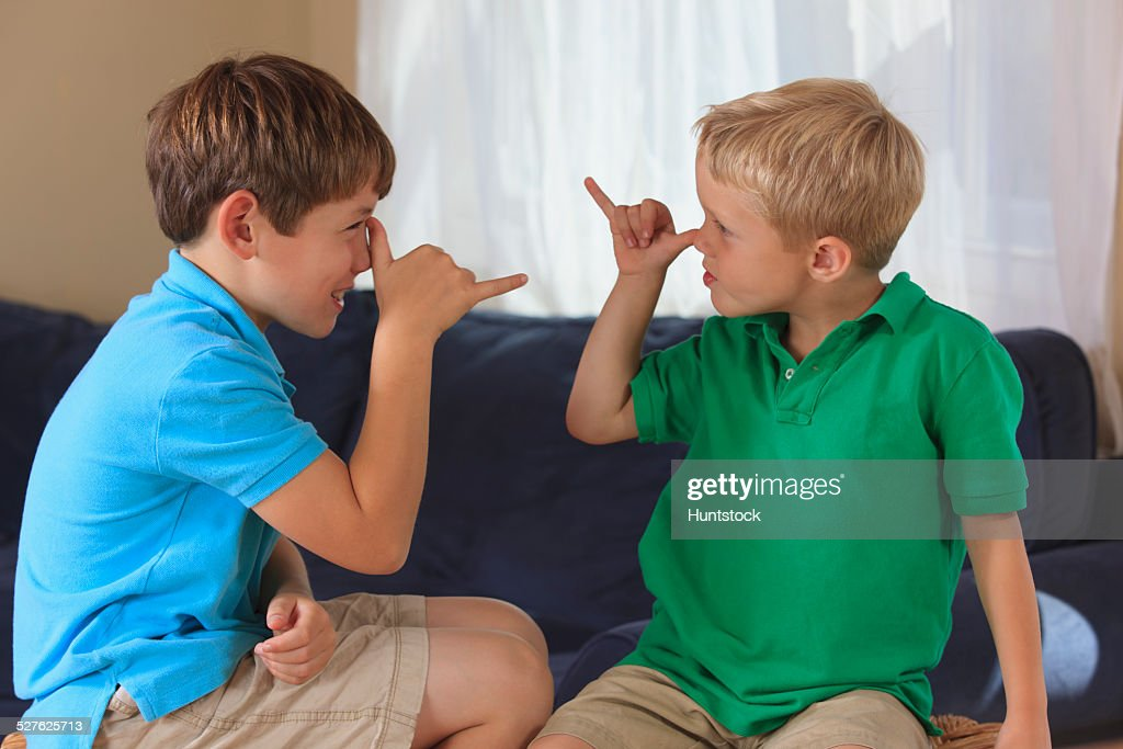 Boys with hearing impairments signing silly in American sign language on their couch : Stock Photo