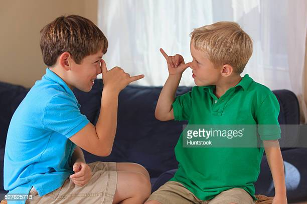 Boys with hearing impairments signing silly in American sign language on their couch