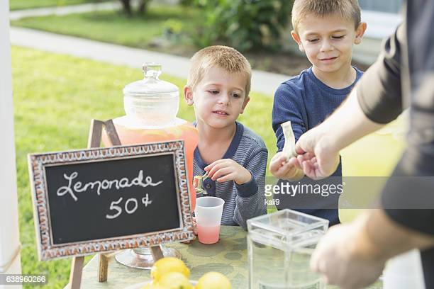 Boys with lemonade stand, taking payment from man