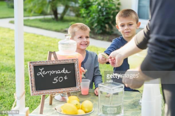 Garçons avec le stand de limonade, prendre le paiement de l'homme