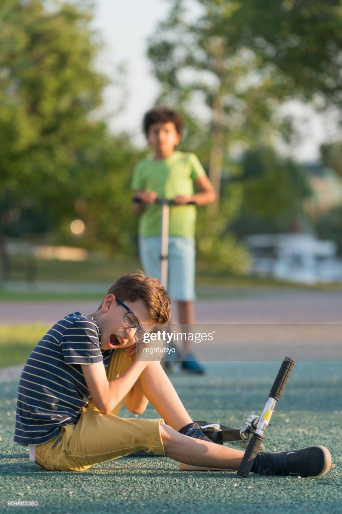 Jungen mit Roller-Unfall in einem park : Stock-Foto