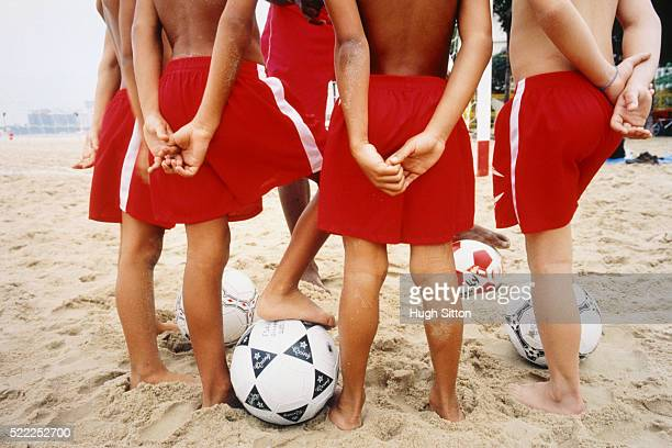 boys with soccer coach on beach - hugh sitton stock-fotos und bilder