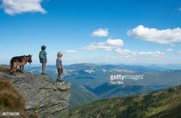 Boys with their dog hiking on mountain summit overlooking panoramic landscape, Rodna Mountain, Maramures, Romania