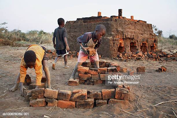 Boys (6-9) working in brick manufacturing industry