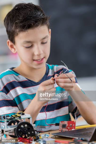 Boys works on robot in after school engineering club