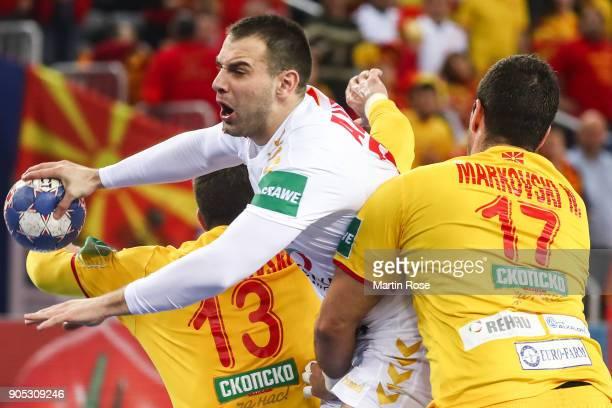 Bozo Andjelic of Montenegro is challenged by Filip Mirkulovski of Macedonia and Nikola Markoski of Macedonia during the Men's Handball European...