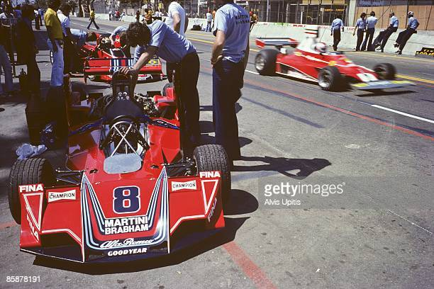 Brabham Alfa Romeo sits in pit lane as the Ferrari 312T of Clay Regazzoni passes by at the first United States Grand Prix West held on March 28 1976...