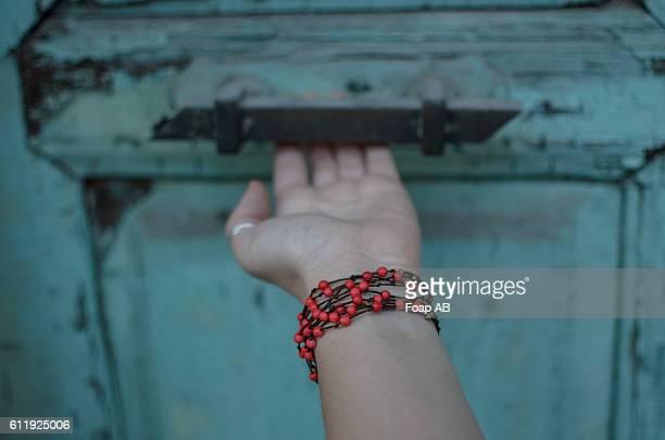 Bracelet in hand opening the old door