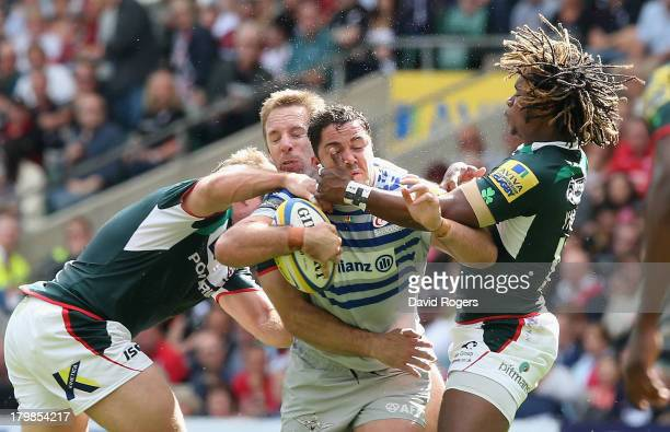 Brad Barritt of Saracens is tackled by Marland Yarde and David Paice during the Aviva Premiership match between London Irish and Saracens at...