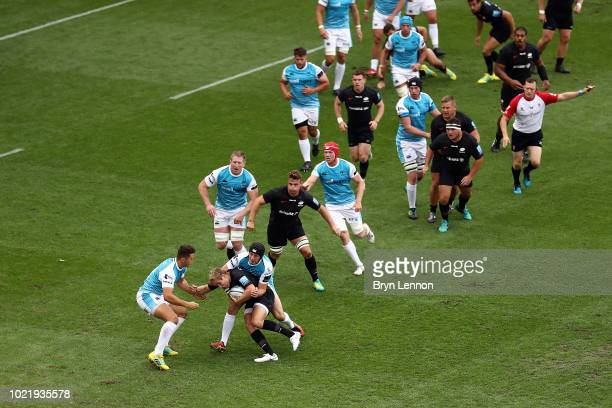 Brad Barritt of Saracens is tackled by Sam Davies of Ospreys during the preseason match between Saracens and Ospreys at the Honourable Artillery...