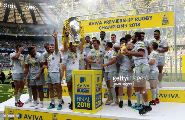 Brad Barritt of Saracens lifts the Aviva Premiership trophy following his side's victory during the Aviva Premiership Final between Saracens and...