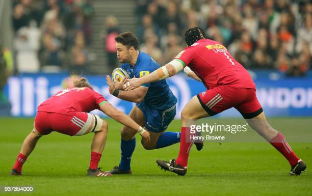 Brad Barritt of Saracens tackled by Luke Wallace of Harlequins and Mark Lambert of Harlequins during the Aviva Premiership match between Saracens and...