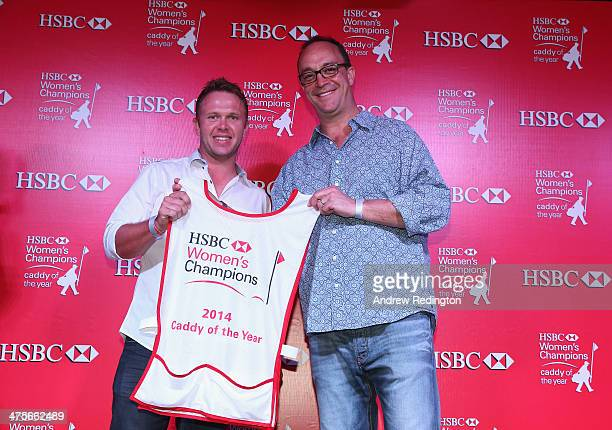 Brad Beecher receives the trophy and caddie bib from Giles Morgan after beiing named the 2014 HBC Caddy Of The Year after the second round of the...