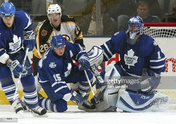 Brad Boyes of the Boston Bruins looks on with Andrew Raycroft and Tomas Kaberle both of the Toronto Maple Leafs as the Leafs' Pavel Kubina takes the...
