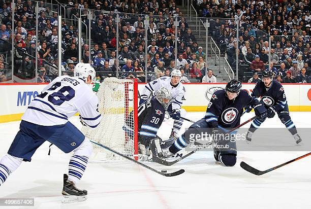 Brad Boyes of the Toronto Maple Leafs shoots the puck towards the net as goaltender Connor Hellebuyck and Jacob Trouba of the Winnipeg Jets defend...