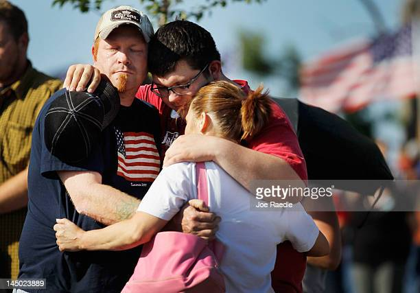 Brad Cooley, Austin Stapleton and Misty Pietrzak hug in Cunningham Park during a moment of silence at 5:41 p.m. Which was when the monstrous tornado...