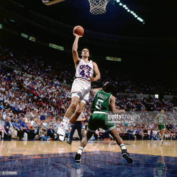 Brad Daugherty of the Cleveland Cavaliers drives to the basket for a layup against John Bagley of the Boston Celtics during an NBA game in 1991 at...
