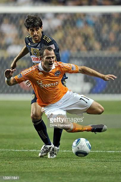 Brad Davis of the Houston Dynamo gets tripped up by Veljko Paunovic of the Philadelphia Union at PPL Park on August 6 2011 in Chester Pennsylvania