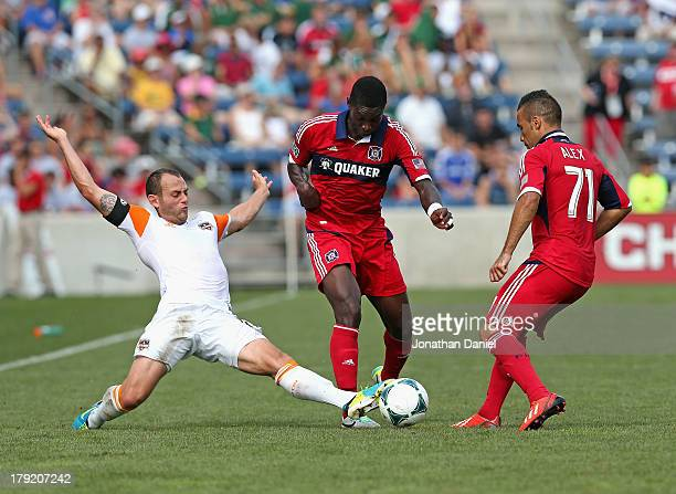 Brad Davis of the Houston Dynamo kicks the ball between Jalil Anibaba and Alex of the Chicago Fire during an MLS match at Toyota Park on September 1...