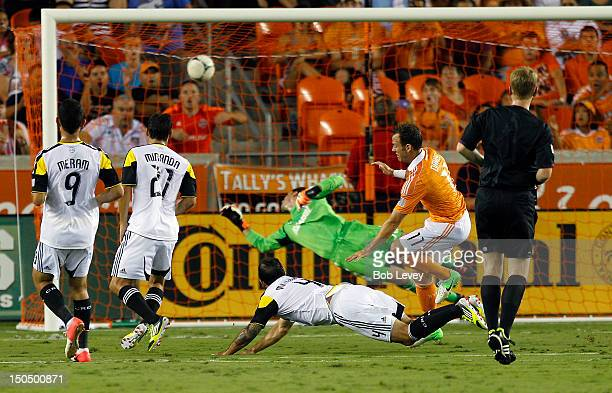 Brad Davis of the Houston Dynamo stumbles over Carlos Mendes of the Columbus Crew after scoring past a diving goalkeeper Andy Gruenebaum of the...