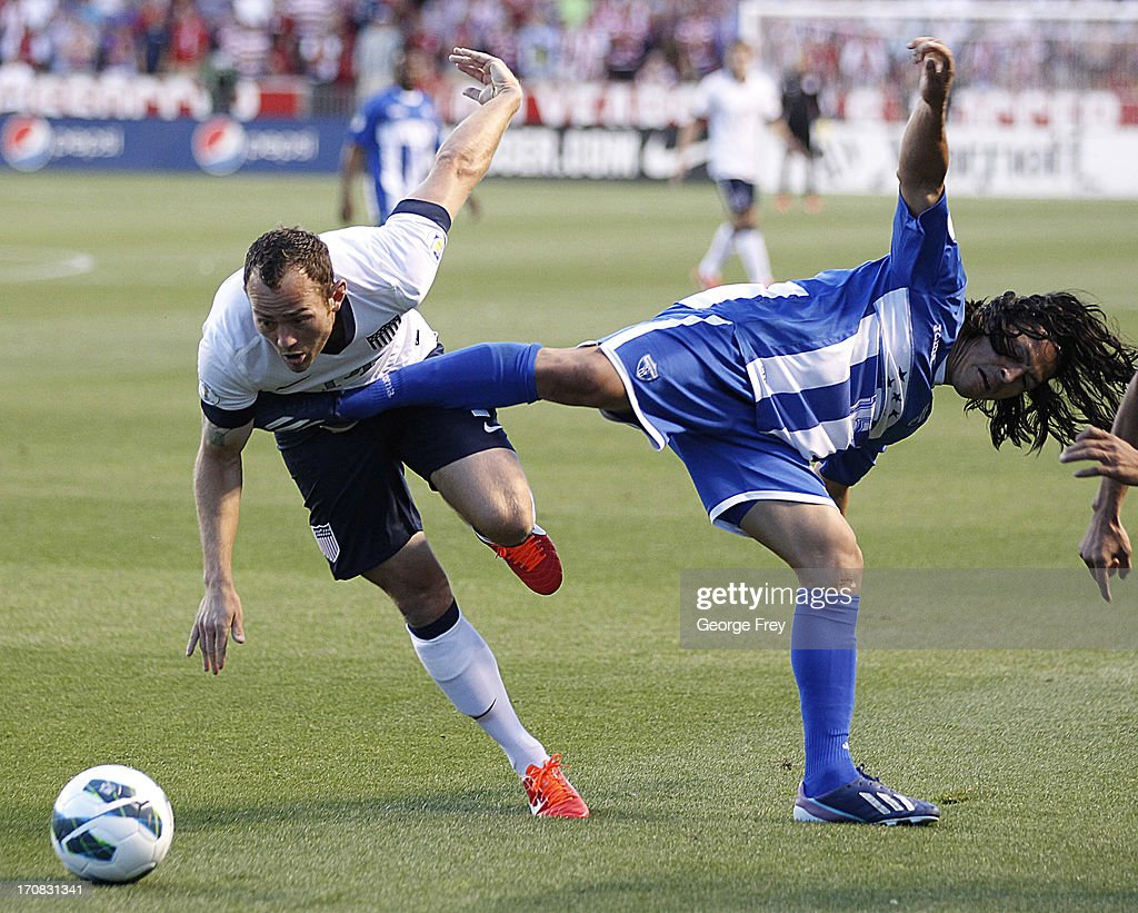Brad Davis #14 of the United States is kicked by Roger Espinoza #15 of Honduras during the second half of a World Cup qualifying match on June 18, 2013 at Rio Tinto Stadium in Sandy, Utah.