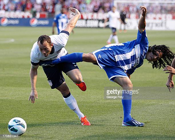 Brad Davis of the United States is kicked by Roger Espinoza of Honduras during the second half of a World Cup qualifying match on June 18 2013 at Rio...