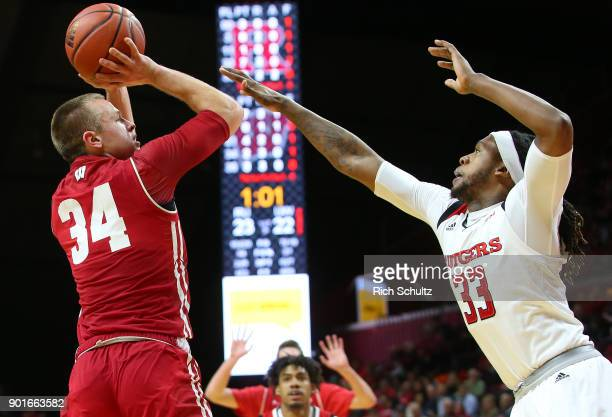 Brad Davison of the Wisconsin Badgers attempts a shot as Deshawn Freeman of the Rutgers Scarlet Knights defends during the first half of a college...
