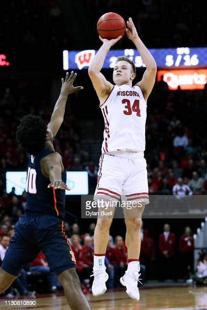 Brad Davison of the Wisconsin Badgers attempts a shot while being guarded by Andres Feliz of the Illinois Fighting Illini in the second half at the...