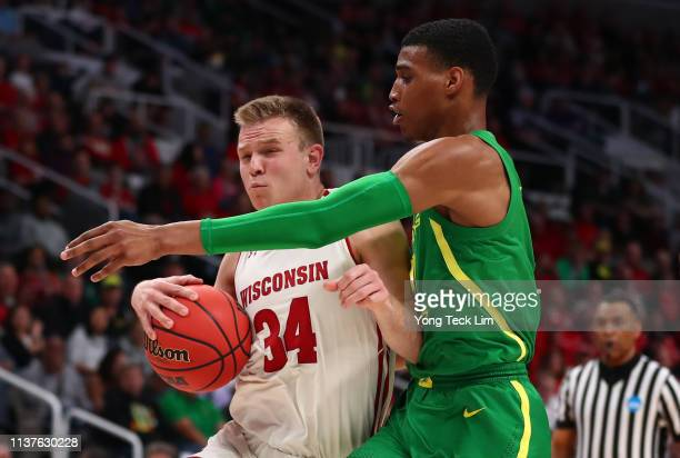 Brad Davison of the Wisconsin Badgers dribbles the ball against Kenny Wooten of the Oregon Ducks in the first half during the first round of the 2019...