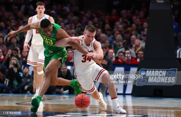 Brad Davison of the Wisconsin Badgers goes for a loose ball against Francis Okoro of the Oregon Ducks in the first half during the first round of the...