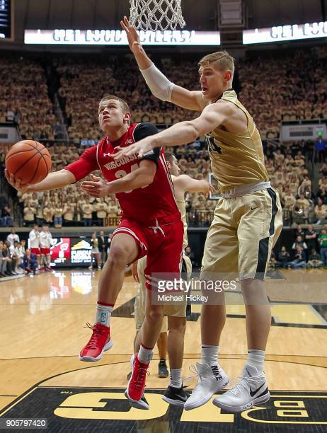 Brad Davison of the Wisconsin Badgers shoots the ball against Isaac Haas of the Purdue Boilermakers at Mackey Arena on January 16 2018 in West...
