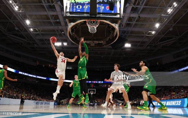 Brad Davison of the Wisconsin Badgers takes a shot against the Kenny Wooten of the Oregon Ducks in the second half during the first round of the 2019...