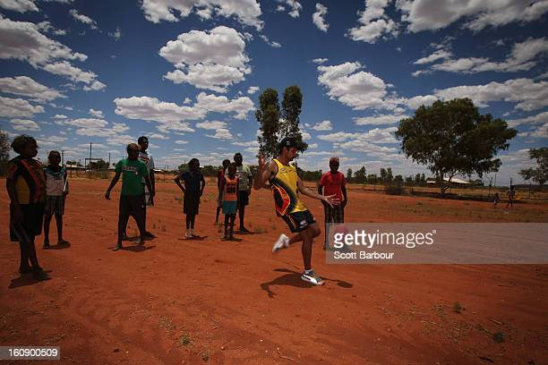 Brad Dick of the Indigenous All Stars kicks a football as members of the Indigenous All Stars visit Yuendumu School in the Australian outback ahead...