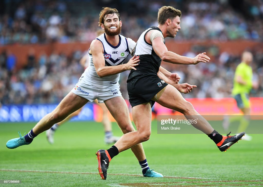 Brad Ebert of Port Adelaide kicks in front of Connor Blakely of the Dockers during the round one AFL match between the Port Adelaide Power and the Fremantle Dockers at Adelaide Oval on March 24, 2018 in Adelaide, Australia.