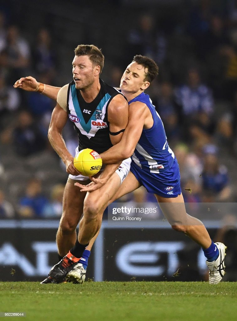 Brad Ebert of the Power handballs whilst being tackled by Ben Jacobs of the Kangaroos during the round six AFL match between the North Melbourne Kangaroos and Port Adelaide Power at Etihad Stadium on April 28, 2018 in Melbourne, Australia.