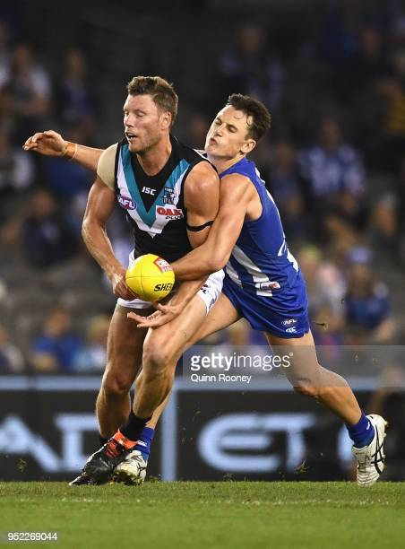 Brad Ebert of the Power handballs whilst being tackled by Ben Jacobs of the Kangaroos during the round six AFL match between the North Melbourne...