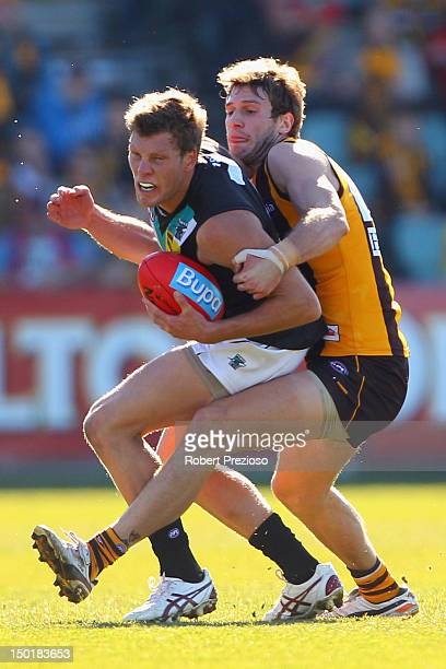 Brad Ebert of the Power is tackled by Grant Birchall of the Hawks during the round 20 AFL match between the Hawthorn Hawks and the Port Adelaide...