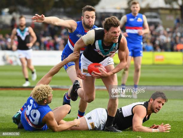 Brad Ebert of the Power is tackled by Jason Johannisen and Matthew Suckling of the Bulldogs during the round 22 AFL match between the Western...