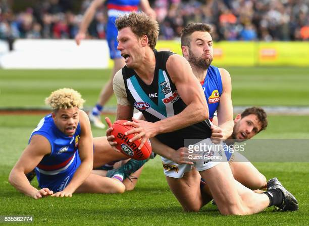 Brad Ebert of the Power is tackled by Matthew Suckling of the Bulldogs during the round 22 AFL match between the Western Bulldogs and the Port...