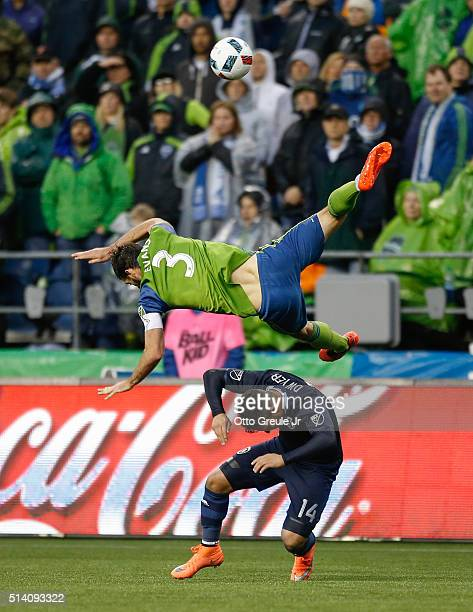 Brad Evans of the Seattle Sounders FC tumbles over Dom Dwyer of Sporting Kansas City at CenturyLink Field on March 6 2016 in Seattle Washington Evans...