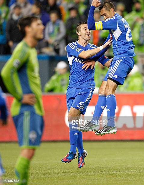 Brad Evans of the Seattle Sounders looks the other way as Jeb Brovsky and Davy Arnaud both of Montreal Impact celebrate Arnaud's goal in the first...