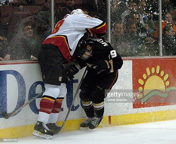 Brad Ference of the Calgary Flames checks Andy McDonald of the Anaheim Ducks during their contest at the Honda Center on December 18 2006 in Anaheim...