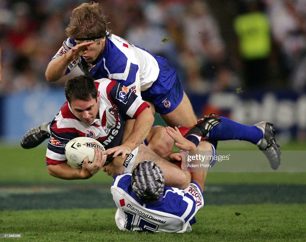 Brad Fittler of the Roosters is smashed during the NRL Grand Final between the Sydney Roosters and the Bulldogs held at Telstra Stadium, October 3, 2004 in Sydney, Australia.