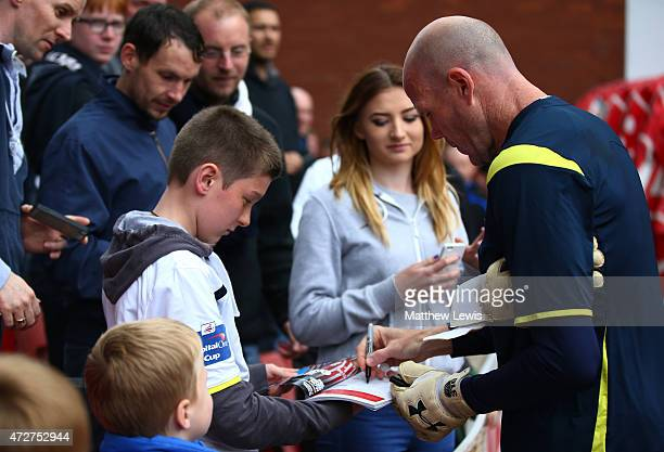 Brad Friedel of Spurs signs autographs prior to the Barclays Premier League match between Stoke City and Tottenham Hotspur at Britannia Stadium on...